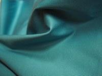 Baumwollstoff in blaugrüner Farbe einfärbig in Faltenwurf.
