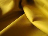 Baumwollstoff in gelb-grüner Farbe einfärbig in Faltenwurf.