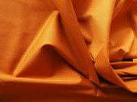 Baumwollstoff in kupferroter Farbe einfärbig in Faltenwurf.