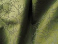 Baumwollstoff in graugrüner Farbe mit aufgedrucktem Flechtenmuster in Faltenwurf.